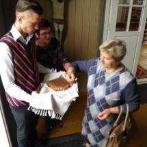 Mokiniai pašventinta duona vaišino parapiečius.